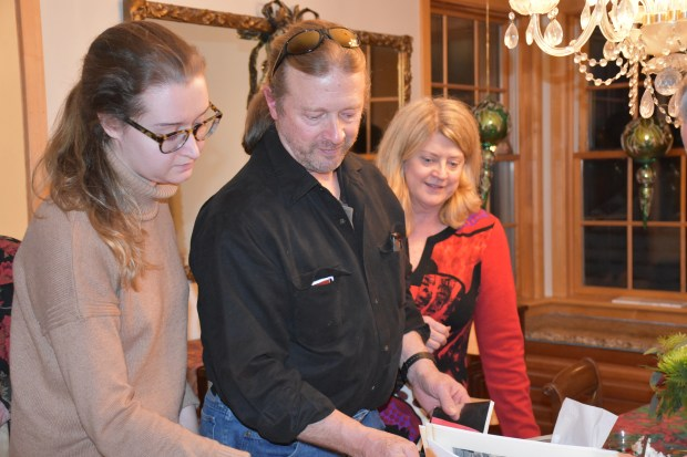 Lucy Kane, left, with her uncle Scott Anderson and aunt Carrie Anderson-Snyder look through writings by Lucy's mother Holly Anderson, local poet and 9/11 survivor. (Deanna Weniger/Pioneer Press)