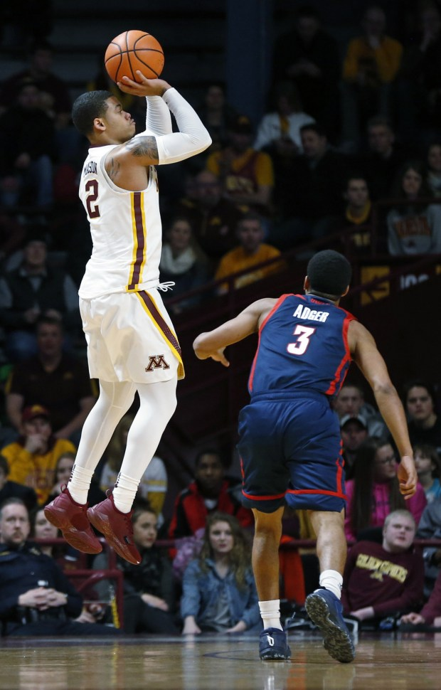 Minnesota's Nate Mason, left, shoots as Florida Atlantic's Anthony Adger watches in the first half Saturday, Dec. 23, 2017, in Minneapolis. (AP Photo/Jim Mone)