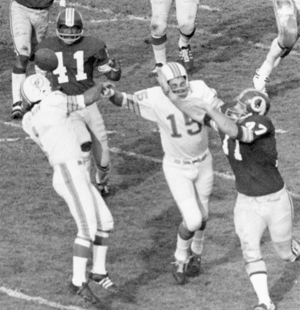 FILE - In this Jan. 14, 1973, file photo, Washington Redskins Mike Bass (41) gets the ball which is deflected out of Garo Yepremian's hands, left, during the Super Bowl in Los Angeles. Yepremian had his kick blocked, the ball bounced back to him and then he tried to pass but the ball was deflected towards Bass, who caught it and ran it in for a touchdown. (AP Photo/File)