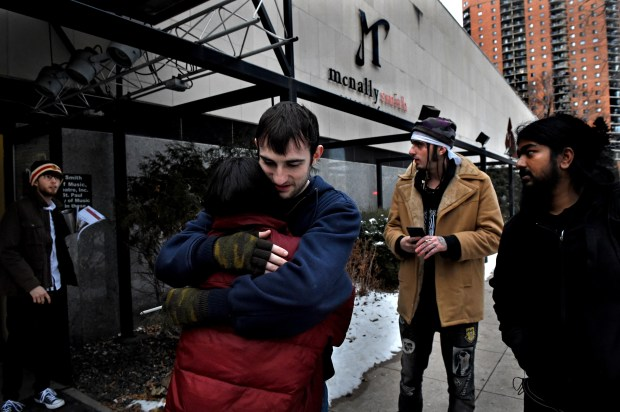 Alec Thicke, center, a production major at McNally Smith College of Music with one semester left of school, hugs Andie Fonseca, a production major that had two semesters left, outside of the school on Dec. 15, 2017. The previous day it was announced the college would close. Second from the right is Jozzy OG, (tan coat), a hip-hop major with one semester left who was about to start a piano performance major.  (Jean Pieri / Pioneer Press)