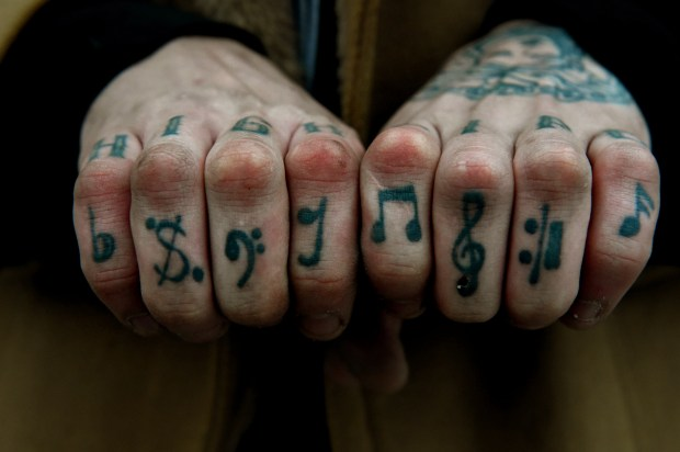 """Jozzy Og shows his tattoos Friday, Dec. 15, 2017, after it was announced McNally Smith College of Music will close after fall semester 2017. """"It's a death of a lot of dreams, of a big music family,"""" he said. He had one semester left and was about to start a piano performance major. (Jean Pieri / Pioneer Press)"""
