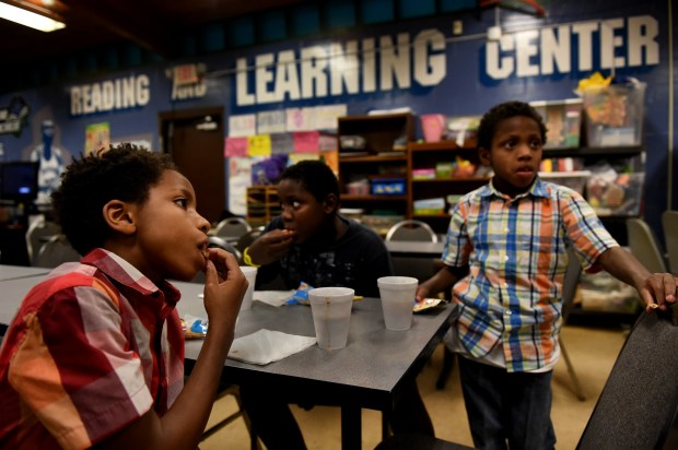 From left, Dequan Mathews, 11, Davion George, 12, and Donntrell Mathews, 7, eat freshly baked sugar cookies in the activity room after playing basketball at Scheffer Recreation Center in St. Paul on Thursday, Dec. 14, 2017. St. Paul's newest giant recreational facility will be 23,500 square feet and will replace the aging 6,600 square foot structure in Frogtown. (Jean Pieri / Pioneer Press)