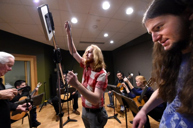 Matthew Grosso, center, and Elijah Deaton-Berg, right, set up microphones in a recording studio at McNally Smith College of Music in St. Paul on Wednesday, October 7, 2015. Eva Beneke's guitar students are joined by John Black's engineering students in the performance studio and control room. In the past, performance students would not have learned alongside technical students.  (Pioneer Press: Jean Pieri)