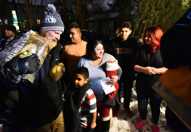 Clarissa Benitez, center, watches as dozens of community members sing Christmas carols and deliver presents to Benitez and her family, on Thursday, Dec. 21, 2017. Benitez's son Miguel Gonzalez, 16, a Harding High School student, died after falling ill in September. (Pioneer Press / John Autey)