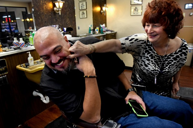 "During a quiet time between customers, Pat Link, right, goofs around with shop owner Gil Garcia at Signal Barbers in West St. Paul Friday, Dec. 15, 2017. ""He grew up coming here. When I found out he was going to barber school I said I would hire him,"" said Link. ""And I did."" Garcia bought the shop from Link in 2011. (Jean Pieri / Pioneer Press)"