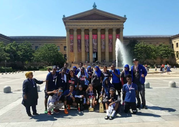 Hani Haybe, left, and Soren Smogard-Ayers, right wearing cap, pose with members of Street Soccer Twin Cities team after they won trophies at a tournament held in Philadelphia in June 2017. Haybe, a surgical technician, founded a free soccer program for disadvantaged and at risk immigrant youths seven years ago. (Courtesy of Street Soccer Twin Cities)