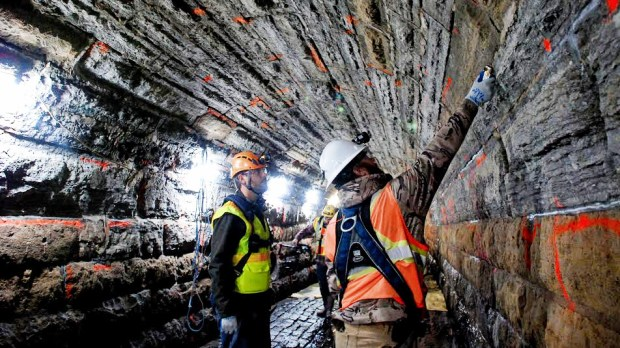 Workers with the Capitol Region Watershed District inspect mortar between the limestone blocks of the Trout Brook Storm Sewer system in St. Paul. (Courtesy of Capitol Region Watershed District)