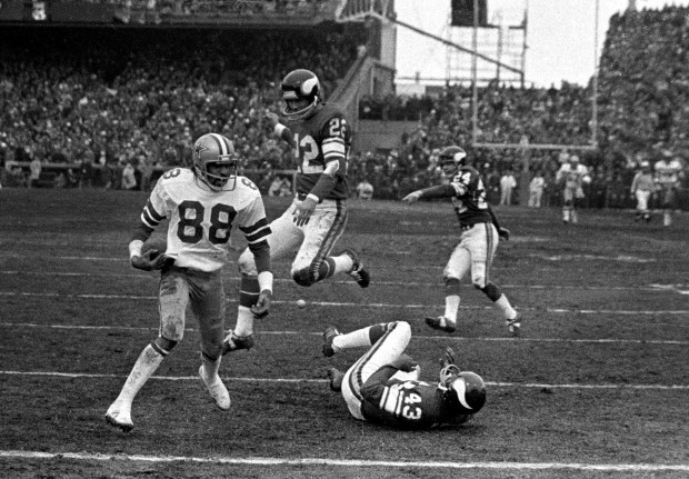 Dallas Cowboys wide receiver Drew Pearson (88) nears the end zone after catching a game-winning 50-yard touchdown pass from quarterback Roger Staubach in the fourth quarter of a NFC divisiional playoff game against the Minnesota Vikings at Metropolitan Stadium in Bloomington, Minn. on Dec. 28,1975. Vikings defenders Nate Wright (43) and Paul Krause (22) are in on the play. (Associated Press)