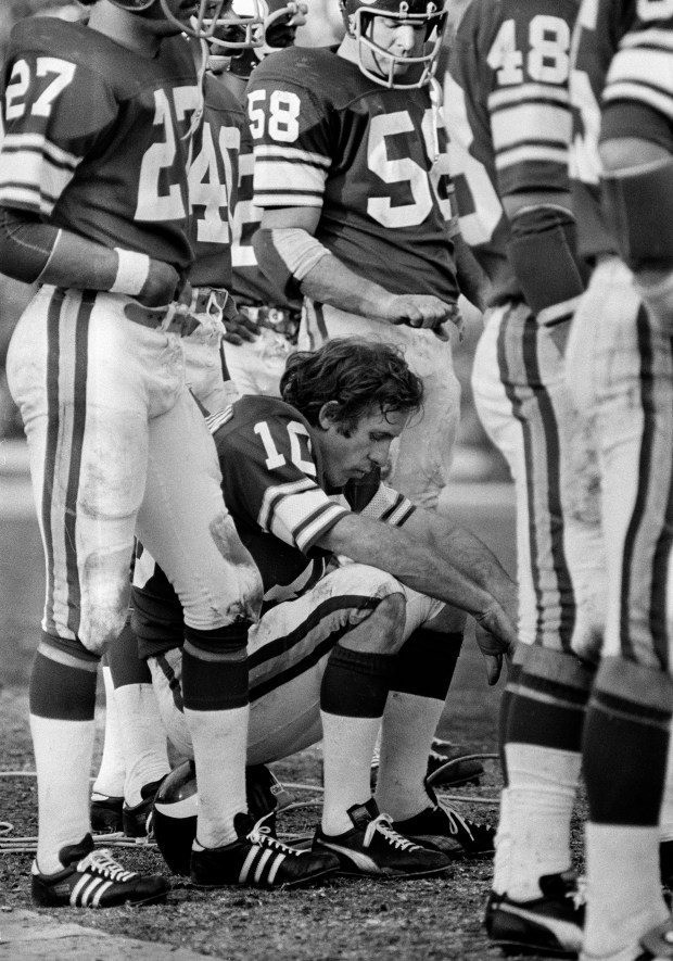 Minnesota Vikings quarterback Fran Tarkenton, finishing his fourth Super Bowl without a win, sits on his helmet during the final minutes as his team fell to the Oakland Raiders 32-14 in Super Bowl XI, Jan. 9, 1977, in Pasadena, Calif. (Associated Press)