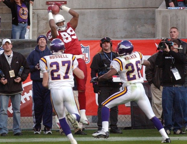 Arizona's Nathan Poole pulls in a 28-yard touchdown pass from quarterback Josh McCown as time runs out Sunday, Dec. 28, 2003 at Sun Devil Stadium in Tempe, Ariz. The Cardinals won 18-17 to eliminate the Vikings from the playoffs. Defending for the Vikings are Brian Russell (27) and Denard Walker (26). (Joe Rossi / Pioneer Press)