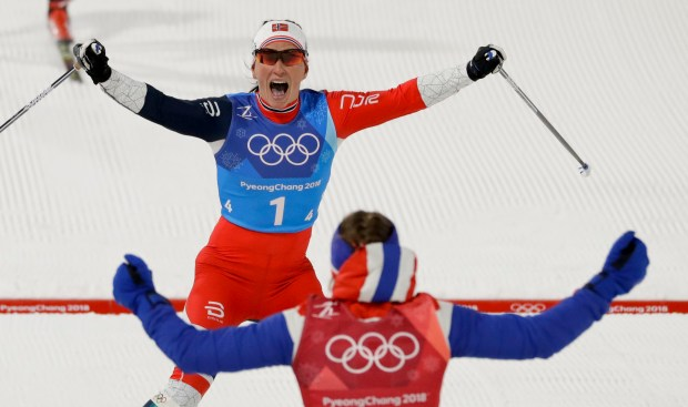 Marit Bjoergen, top, of Norway, celebrates with Ingvild Flugstad Oestberg after winning the women's 4 x 5km relay cross-country skiing competition at the 2018 Winter Olympics in Pyeongchang, South Korea, Saturday, Feb. 17, 2018. (Kirsty Wigglesworth / Associated Press)