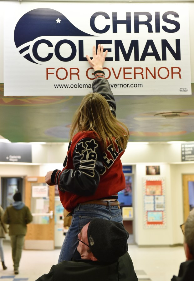 "Francis ""Frankie"" Cerkvenik tries to get a poster for Chris Coleman to stick to the wall as she is held by her dad, Steve, at the St. Paul DFL Caucus at Capitol Hill Magnet School in St. Paul on Tuesday, Feb, 6, 2018. (John Autey / Pioneer Press)"