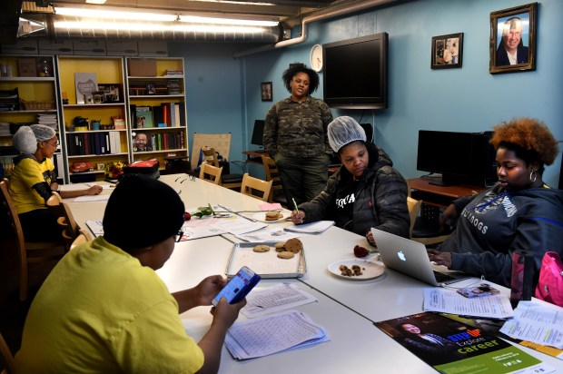 Tanika Reese, a job coach, talks to teens in the youth training program in the computer lab at Cookie Cart in Minneapolis Thursday, Feb. 14, 2018. (Jean Pieri / Pioneer Press)