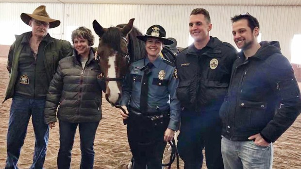Craig and Barb Rutschow, at left, donated their horse, Moose, to the St. Paul police department. They are the parents of St. Paul officer Cohlman Rutschow, second from the right. Officer Jennifer Mink will be paired with Moose. Cohlman's brother, Clayton Rutschow, is on the far right. There was a retirement ceremony on Thursday, Feb. 15, 2018, for Moose's predecessor. (Courtesy of St. Paul police)