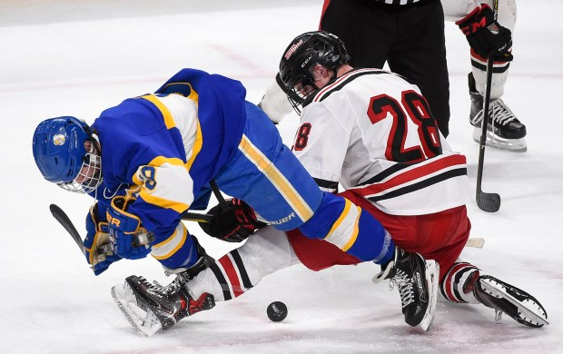 Duluth East forward Logan Anderson, right, and St. Michael-Albertvilleforward Luc Laylin get tangled up as they battle for the puck in the first period of the the Class 2A tournament quarterfinal at Xcel Center Thursday, March 8, 2018. (Photo/Craig Lassig)