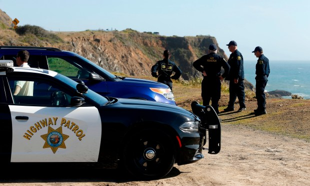 In this March 28, 2018, photo, California Highway Patrol officers and deputy sheriffs from Mendocino and Alameda counties gather after a search for three missing children at the site where the bodies of Jennifer and Sarah Hart and three of their adopted children were recovered two days earlier, after the family's SUV plunged over a cliff at a pullout on the Pacific Coast Highway near Westport, Calif. Three of the children, Devonte Hart, 15, Hannah Hart, 16, and Sierra Hart, 12, have not been found. Authorities say a woman who drove off California cliff last month in an SUV carrying her wife and children was drunk. California Patrol Capt. Bruce Carpenter said Friday, April 13, 2018, that toxicology tests found Jennifer Hart had an alcohol level of .102. California drivers are considered drunk with a level of 0.08 or higher. Authorities don't know who was at the wheel at the time of the accident. (Alvin Jornada/The Press Democrat via AP)
