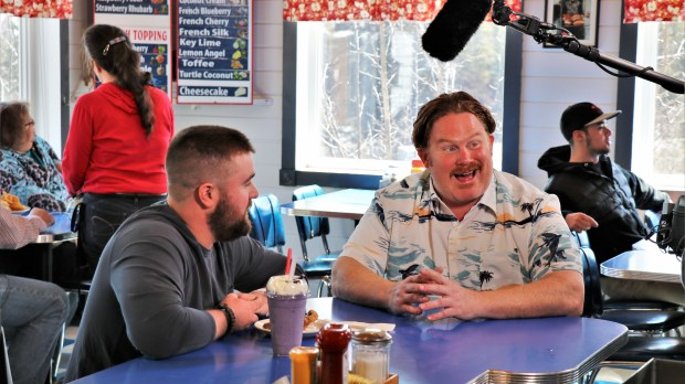 "Casey Webb, right, host of the Travel Channel's ""Man v. Food,"" films an interview with Ethan Casady of Two Harbors at Betty's Pies for an upcoming episode. Casady attempted the ""Pig's Trough"" food challenge, but had to quit after 14 minutes. (Jimmy Lovrien / Forum News Service)"