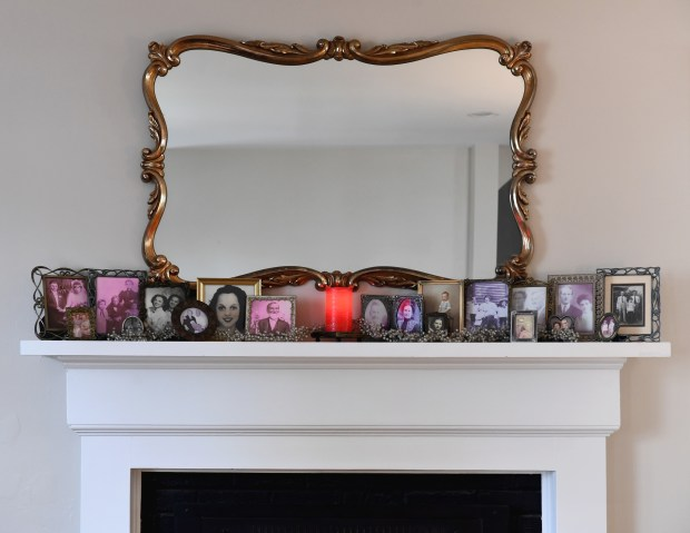 Family photos line the mantel of the Gibbs-Smith multigenerational household. Pew Research found that 20 percent of Americans -- 64 million people -- lived in multigenerational homes in 2016. (Katherine Frey/The Washington Post)