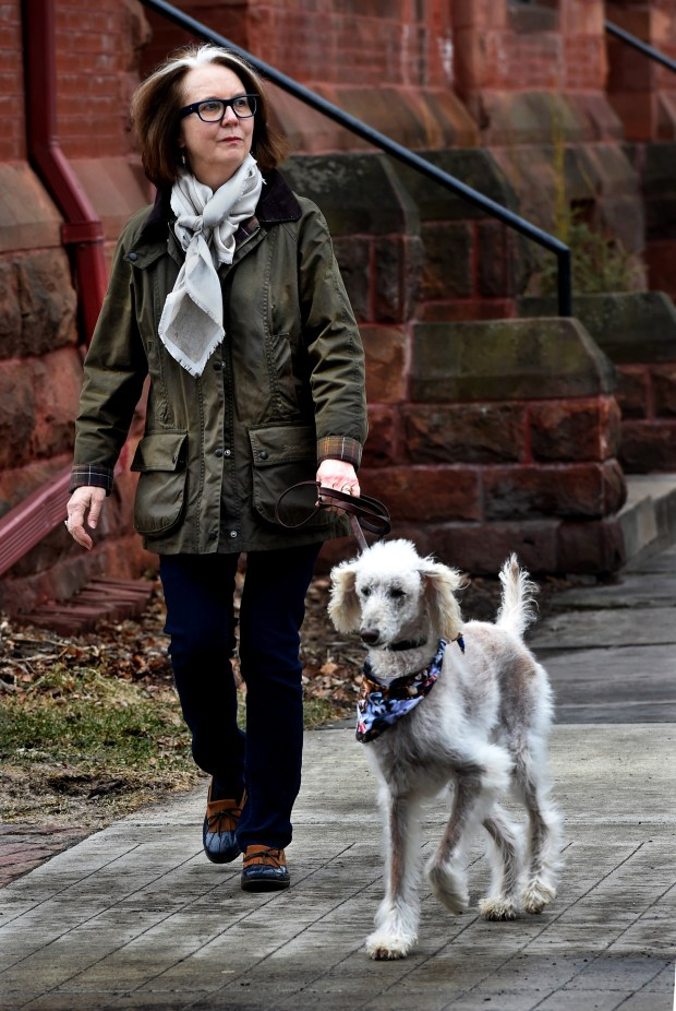 Patricia Hampl, Wednesday, March 28, 2018, walks her standard poodle, Coco, four times a day. In the background is the brownstone row house she lives in. Her new book, 'The Art of the Wasted Day,' was finished at the yellow table in her kitchen. She said a lot of the book refers to the table. (Jean Pieri / Pioneer Press)