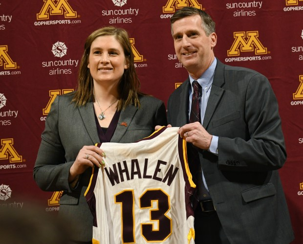 Lindsay Whalen, joined by athletic director Mark Coyle, holds up a jersey with her name on it as she is introduced as the new University of Minnesota women's basketball coach at Williams Arena in Minneapolis on Friday, April 13, 2018. (John Autey / Pioneer Press)