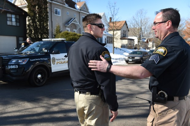 Mental Health Program Director Jamie Sipes, right, says goodbye to mental health officer Justin Tiffany, after they conferred at a possible crisis scene in St. Paul on Wednesday, March 14, 2018. Last year the mayor agreed to add four new officers to the St. Paul police budget for 2018 to form a mental health unit. (Jean Pieri / Pioneer Press)