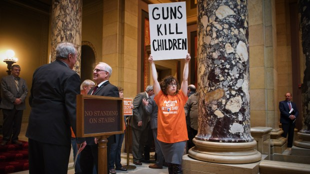 Marti Priest, of Hopkins, with Protect Minnesota, holds her sign outside the Senate Chamber, Thursday, April 26, 2018 as the Senate hears the Omnibus Supplemental Budget Bill in St. Paul. Sen. Ron Latz hopes to attach two gun violence prevention amendments to the judiciary and public safety section of the omnibus bill. (Tom Olmscheid / WorkingPress Photo Agency)