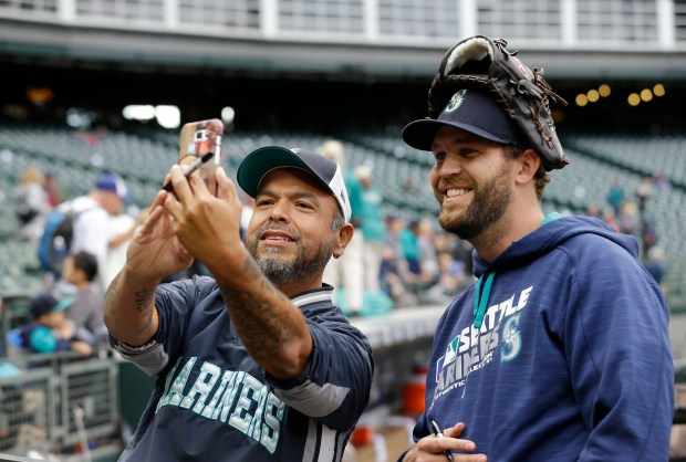 A fan takes a photo with Seattle Mariners pitcher Tom Wilhelmsen, right, before a baseball game against the Oakland Athletics, Saturday, Oct. 1, 2016, in Seattle. (AP Photo/Ted S. Warren)