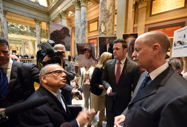Vijay Dixit, left, whose daughter Shreya died in a distracted-driving crash, talks with Minnesota Senate Majority Leader Paul Gazelka, R-Nisswa, about a proposed hands-free driving law as supporters of the bill hold up signs outside the Senate chamber at the State Capitol in St. Paul Thursday, May 10, 2018. Shreya Dixit, of Eden Prairie, was 19 when she was killed while the passenger of a vehicle Nov. 1, 2007. (Dave Orrick / Pioneer Press)