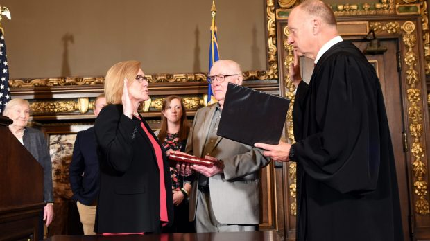 Minnesota Lt. Gov. Michelle Fischbach, left, takes the oath of office as administered by Minnesota Supreme Court Associate Justice G. Barry Anderson as Fischbach's father, Tom St. Martin, holds a family Bible in the Governor's Reception Room at the State Capitol in St. Paul Friday, May 25, 2018. Also on Friday, Fischbach resigned her Senate seat representing the Paynesville-based 13th District. Fischbach, a Republican who was also president of the state Senate, ascended to the lieutenant governor's seat in January after Dayton, a Democrat, appointed then-Lt. Gov. Tina Smith to replace U.S. Sen. Al Franken, who resigned. Fischbach refused to give up her Senate seat -- or take the oath as lieutenant governor -- until the Legislature adjourned. (Dave Orrick / Pioneer Press)