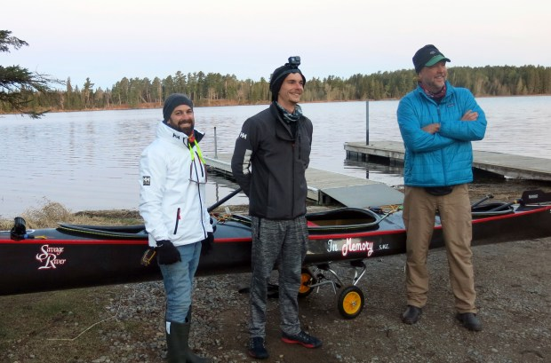 Nate Lastinger, left to right, Kevin Eckelkamp and K.J. Millhone pose for a photo with their custom made, 40 pound canoe before they set off from the Mississippi River headwaters Thursday, May 10, 2018, in Itasca State Park in Minnesota. They're hoping to make it to the mouth of the river in a little more than two weeks - and break the existing world record. (John Enger/Minnesota Public Radio via AP)