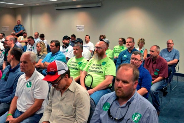 While the Public Utilities Commission goes on a noontime break from its deliberations, Line 3 replacement project supporters, in green T-shirts and with green stickers, mostly remained in the room. Many opponents of the project left the room during the break, which happened shortly after three out of the five commissioners indicated they would likely vote in favor of allowing the project to move forward. (Evan Frost/Minnesota Public Radio via AP)