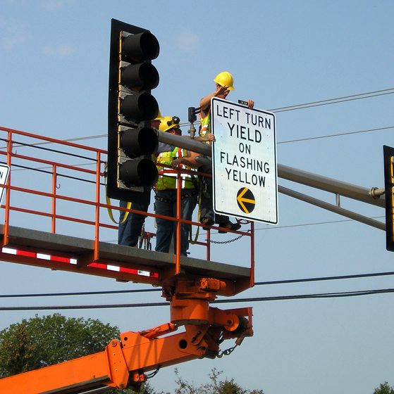 """Traffic engineers install a """"yield on flashing yellow"""" sign. (Courtesy of the Minnesota Department of Transportation)"""