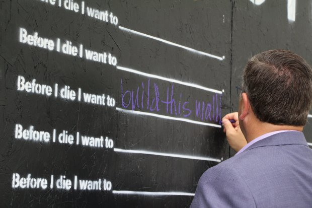 "Scott Mueller, president of Mueller Memorial, writes on the ""Before I Die"" walll he built, along with help from his staff and the White Bear Center for the Arts. The wall, located at Third Street and Bald Eagle Avenue in White Bear Lake, will be open to the public until July 5., 2018 (Maddie DeBilzan / Pioneer Press)"