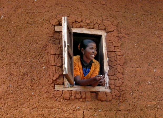 A woman looks out a window in Andranovorivato, Madagascar. The area's houses are made of uncooked brick and clay, and topped with thatched roofs. (Photo by Jeanine Barone For The Washington Post)
