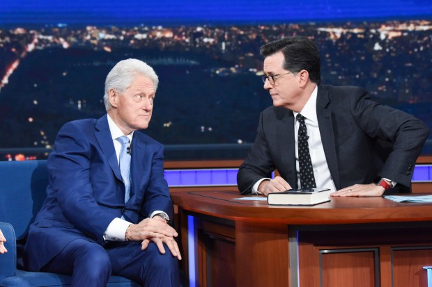 """In this image released by CBS, former President Bill Clinton, left, appears with host Stephen Colbert while promoting his book """"The President is Missing,"""" on """"The Late Show with Stephen Colbert,"""" Tuesday, June 5, 2018 in New York. (Scott Kowalchyk/CBS via AP)"""