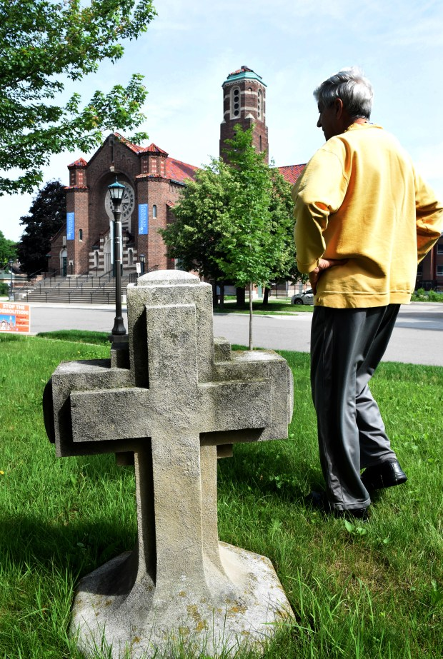 "John Forliti, a retired priest in the Twin Cities, lives across the street from St. Andrew's Church in St. Paul on Wednesday, June 20, 2018. When workers were removing religious insignia when it became a school, he asked the workers what they were going to do with the cross. It now resides on the lawn of his house across the street from the church. ""It's 400 pounds. It's not going anywhere."" He said his family has lived in houses around the church for 97 years."