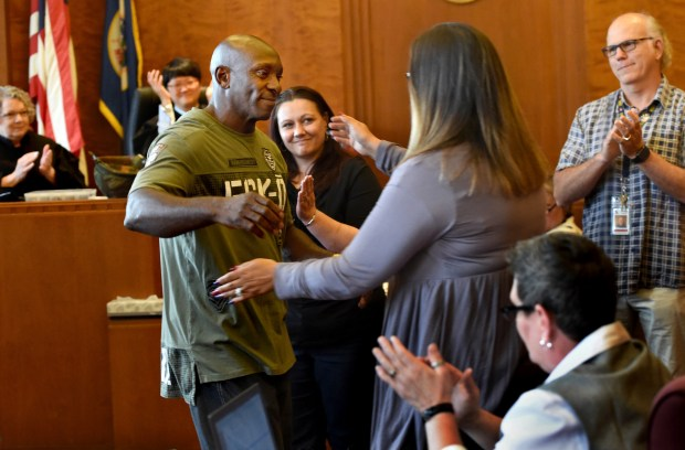 Carl Christian, a 55-year-old Army veteran, is surrounded by supporters as he graduates from Ramsey County Veterans Treatment Court at the Ramsey County Courthouse in St. Paul on Wednesday, July 25, 2018. The intensive, 14-month-long program allows veterans facing crimes to avoid jail or prison as long as they complete aspects of the program. From left, Judge Judith Tilsen, Judge Nicole Starr, Carl's wife, Heidi Christian, Erin Bednarek from Ramsey County Corrections (hugging him), and his mentor, Donn Lindstrom from Ramsey County Veteran's Services, applaud Christian as he graduates. (Jean Pieri / Pioneer Press)