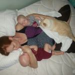 Mama laying in bed with twins