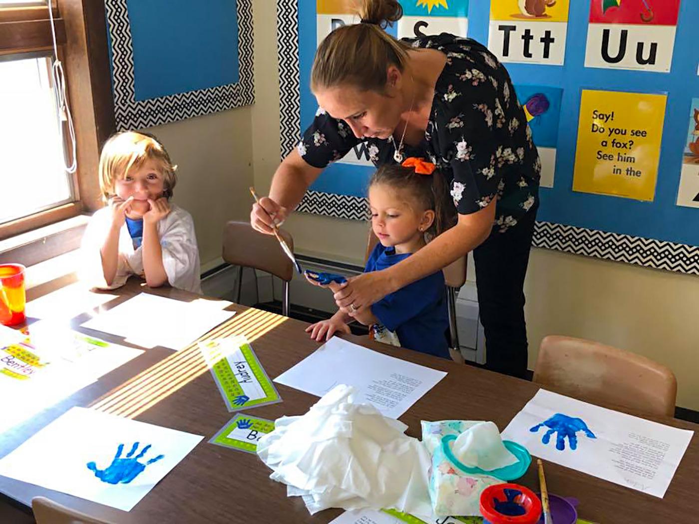 Teacher helping student paint her hand.