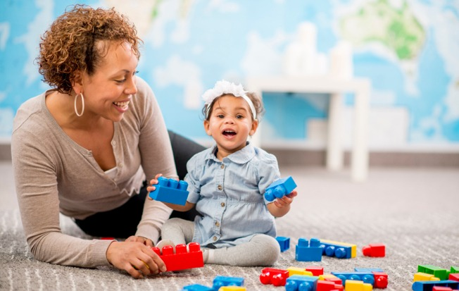Teacher and infant playing with blocks.