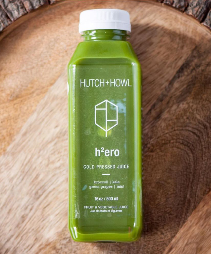 Hutch and Howl green juice in a transparent bottle lying on a woodgrain surface