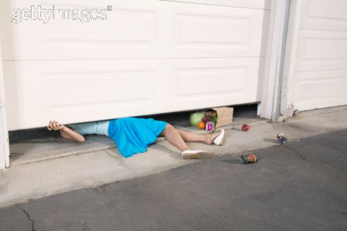 Woman trapped under garage door