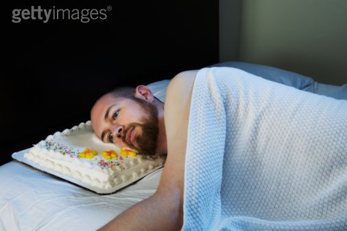 Man laying in bed with cake pillow