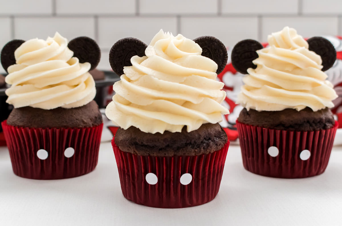 Closeup on three Mickey Mouse Cupcakes with buttercream frosting and red cupcake liners and oreo ears.