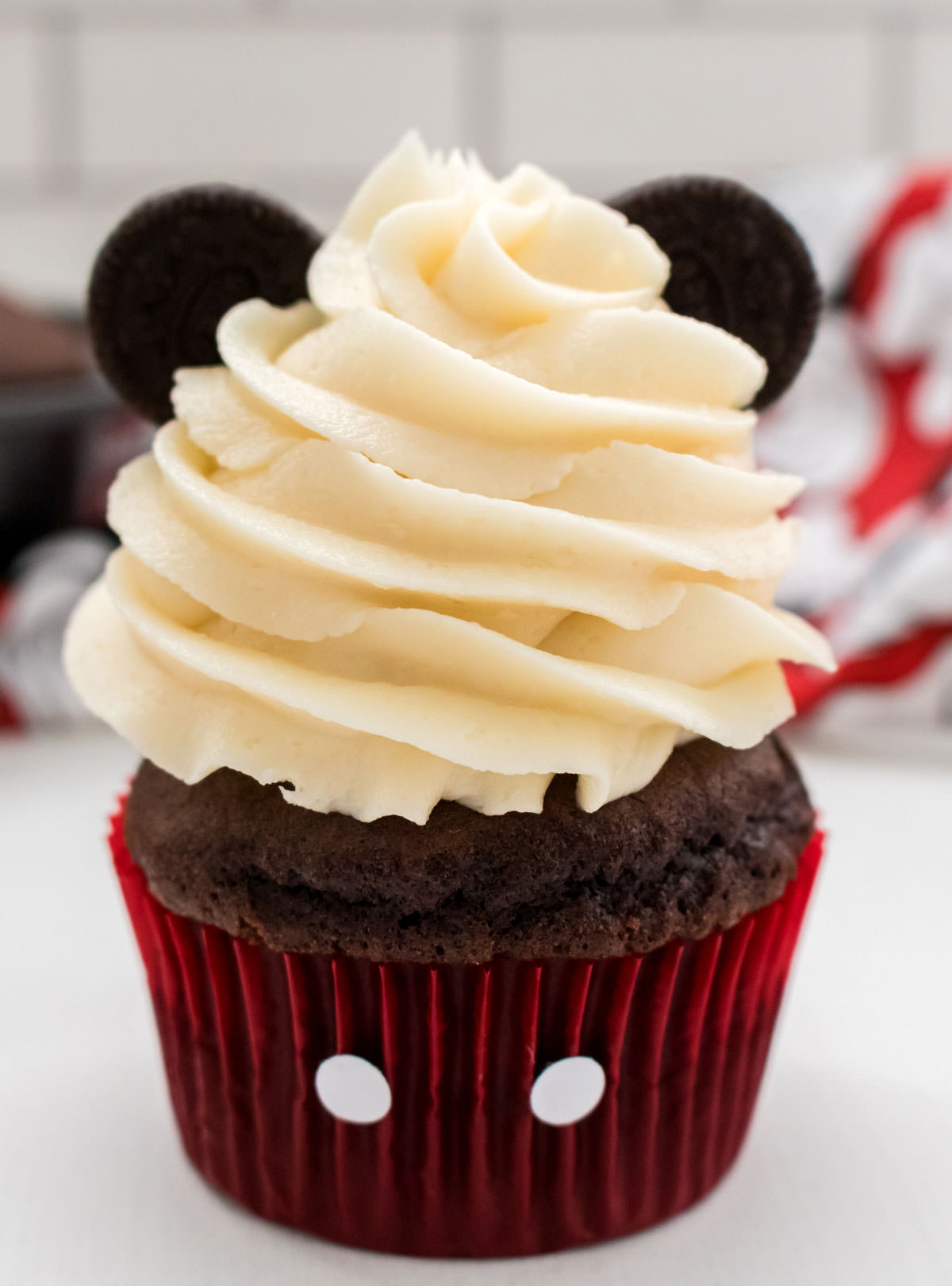 Closeup on a Mickey Mouse Cupcake sitting on a white table in front of a white background, Mickey Mouse Kitchen towel and a pan of cupcakes.