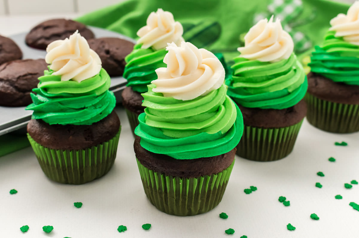 Close up on five chocolate St. Patrick's Day Cupcakes sitting on a white table in front of a green towel and a cupcake pan full of chocolate cupcakes.