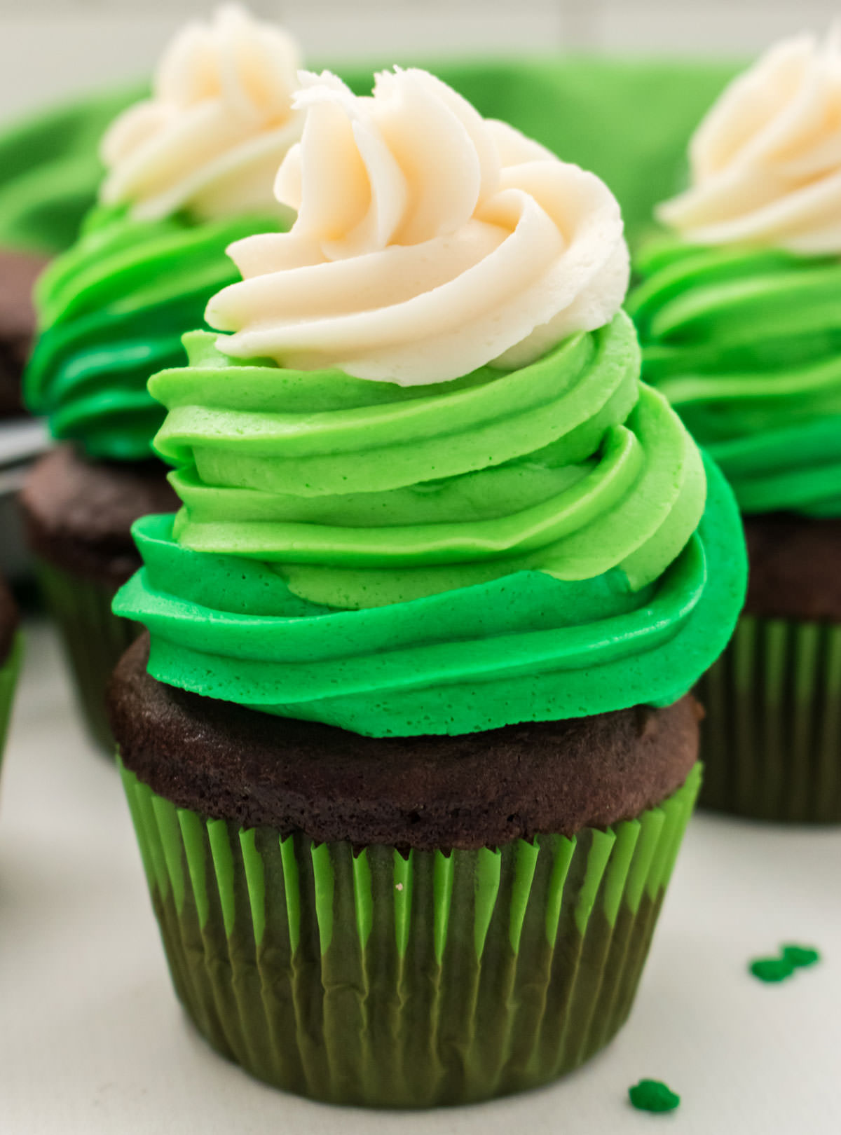 Closeup on a St. Patrick's Day Cupcake featuring a chocolate cupcake with three swirls of dark green, light green and white buttercream frosting.