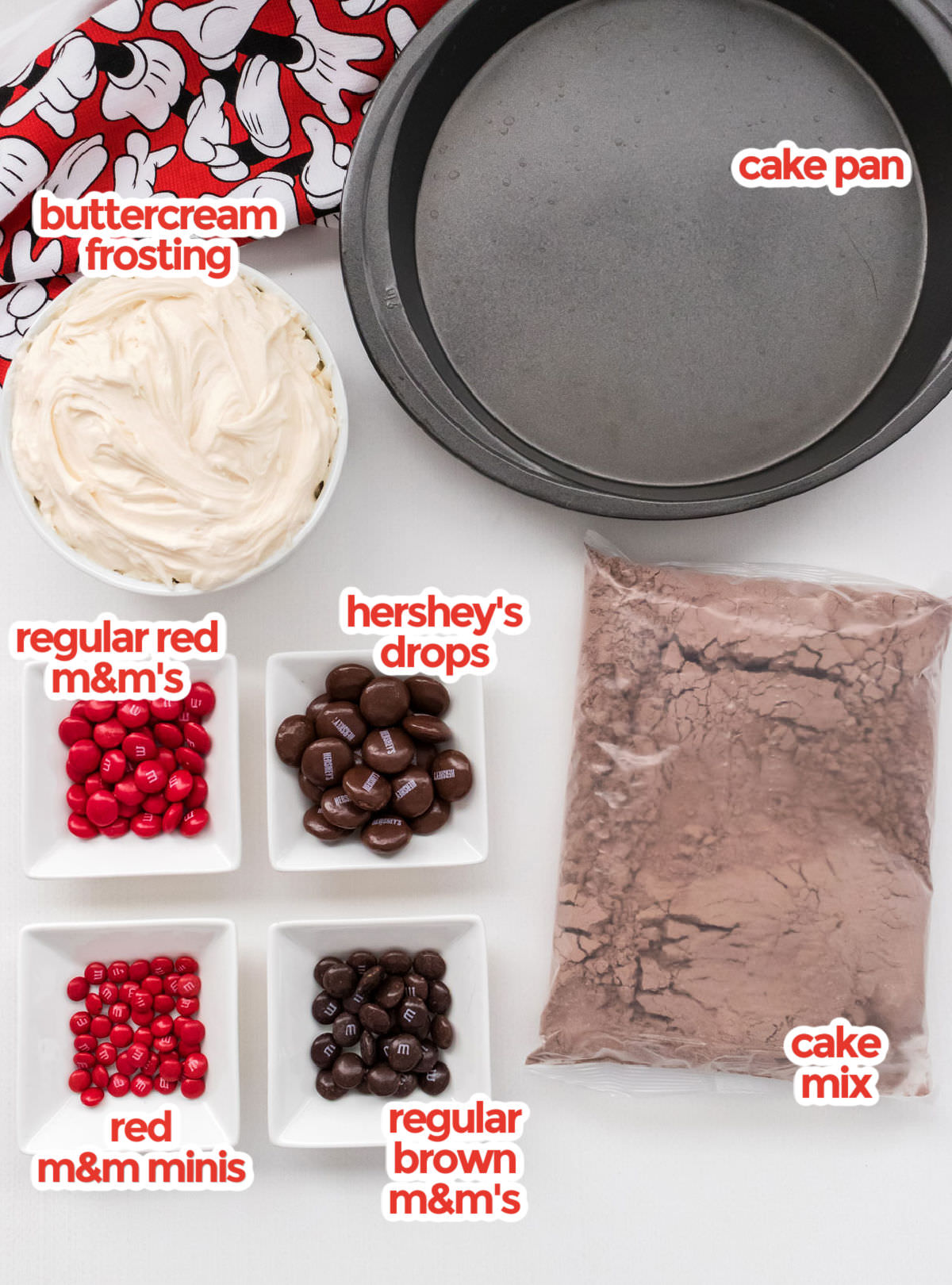 All the ingredients you will need to make an Easy Mickey Mouse Cake including cake mix, cake pans, buttercream frosting, Hershey's Chocolate Drops, Regular M&M's and M&M Minis.