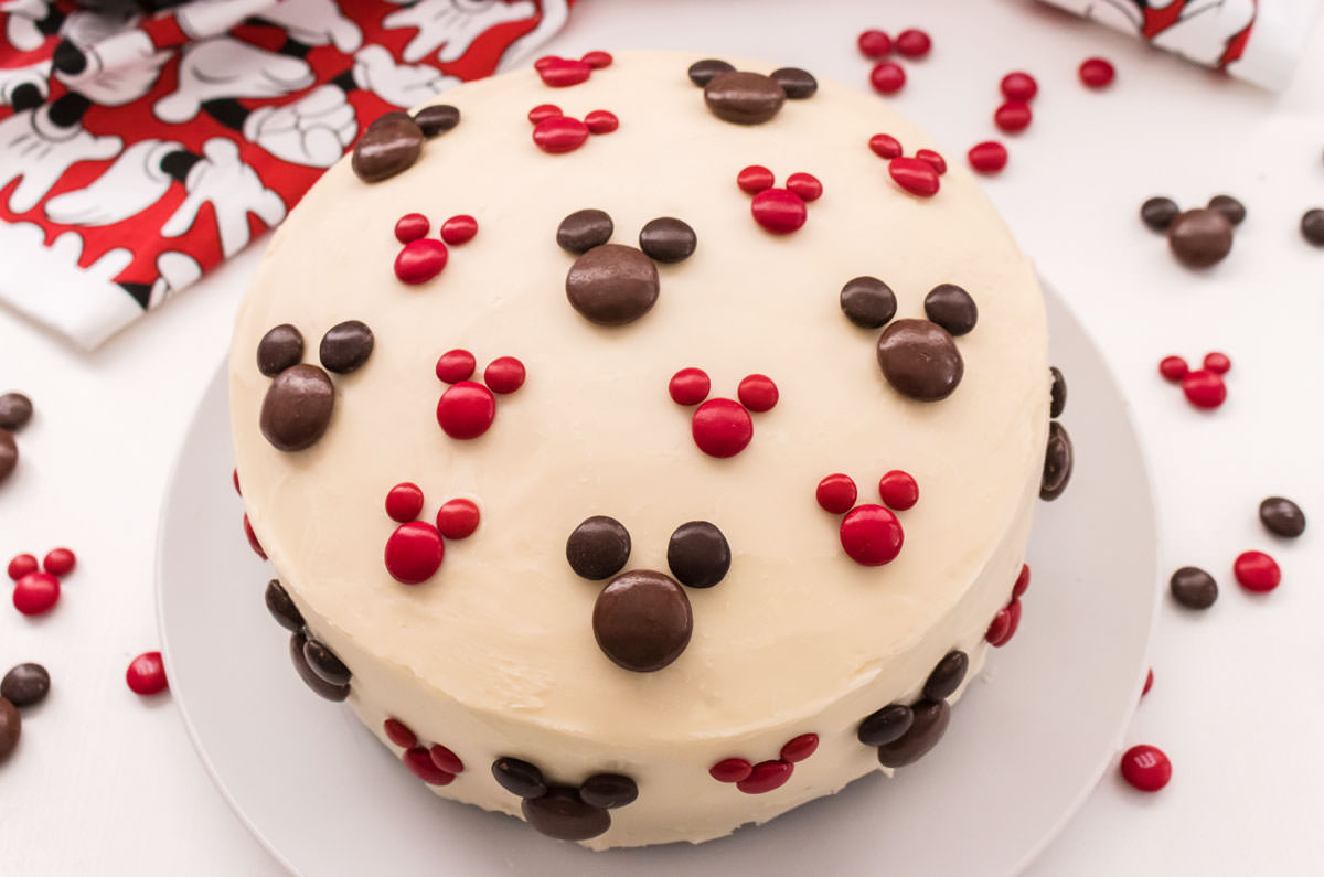 Overhead view of an Easy Mickey Mouse Cake sitting on a white cake plate on a white surface surrounded by M&M's and a Mickey Mouse kitchen towel.