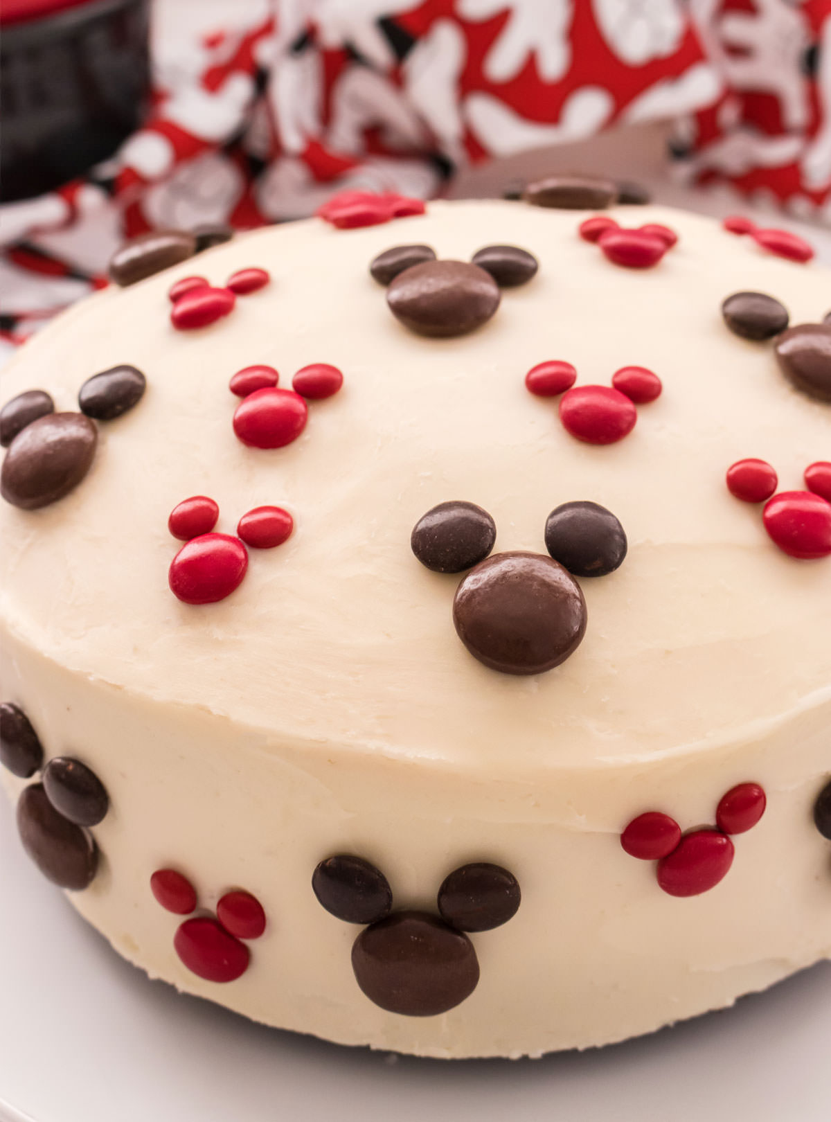 Closeup on an Easy Mickey Mouse Cake sitting on a white surface in front of a Mickey Mouse kitchen towel.